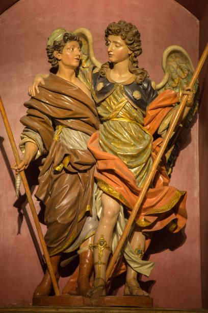 Zaragoza - a polychome esculpida satatue barroca do Arcanjo Raphael com o Tobias na igreja Iglesia de San Miguel de los Navarros. - foto de acervo