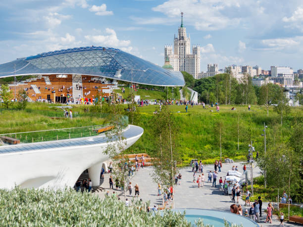 Zaryadye landscape urban park near Red Square. People walking among lawns and flower beds. Glass dome of concert hall with amphitheater. stock photo