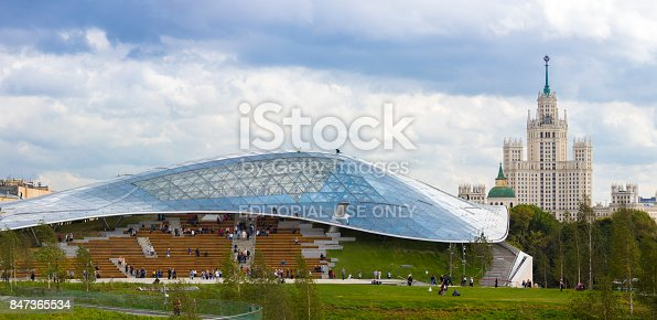 Moscow, Russia - September 14, 2017: Zaryadye Park, main glass dome Concert hall and Stalinist skyscraper Kotelnicheskaya Embankment Building. People on background.