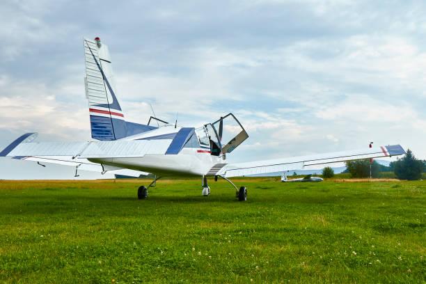 Zbraslavice / Czechia - 08/25/2019: Back view of Zlin Z-43 four-seat airplane standing on a grass runway.  Low-wing monoplane. stock photo