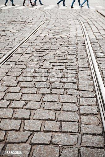 Blurred people zebra crossing on cobblestone pavement. Tramway tracks in foregroundZebra crossing on cobblestone pavement