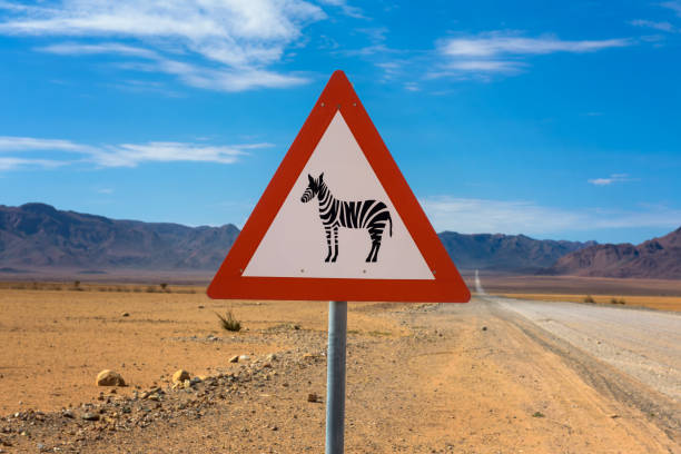 Zebras crossing warning road sign placed in the desert of Namibia stock photo