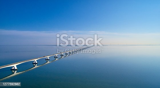 The Zeelandbrug during sunrise. The Sky is blue and it's reflected in the water of the North sea. The bridge is also reflected in the water. Cars drive at a high speed over it.