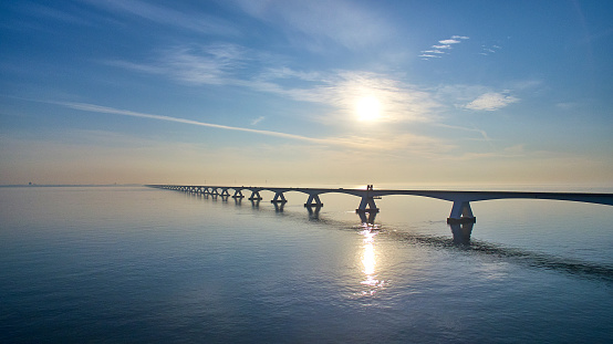 The Zeelandbrug during sunrise. The sun is already a bit higher in the sky and it's reflected in the water of the North sea. The bridge is also reflected in the water. Cars drive at a high speed over it.