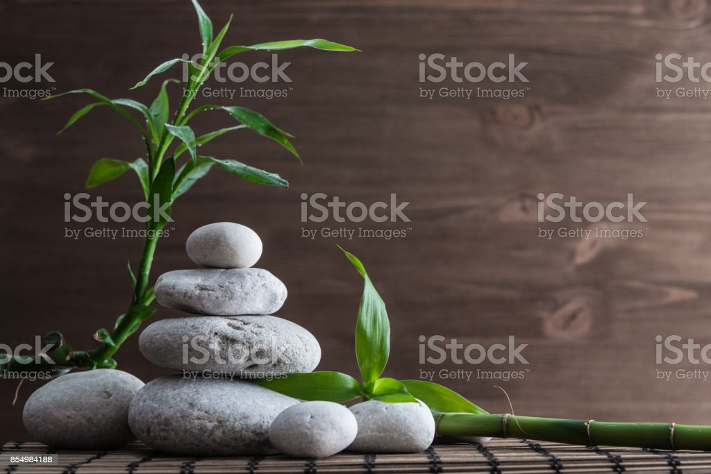 Zen balance stones and bamboo plant on the straw mat stock photo