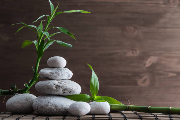 zen balance stones and bamboo plant on the straw mat - naturopathy stock photos and pictures