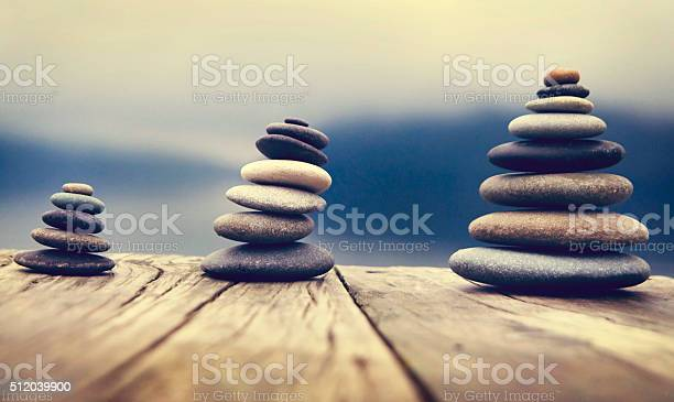 Zen Balancing Pebbles Next To A Misty Lake Concept Stock Photo - Download Image Now