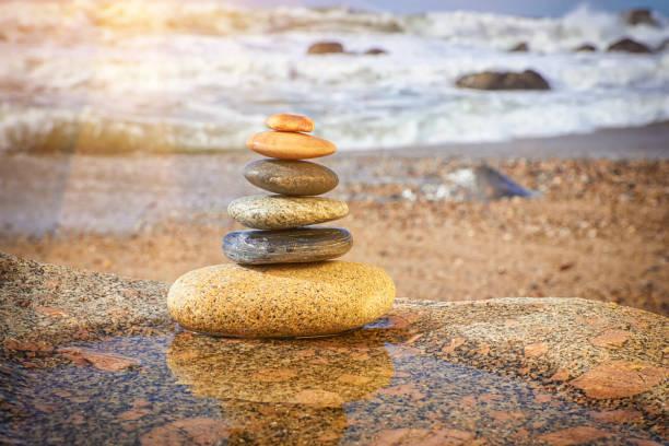 zen balancing pebbles on beach - pyramide sammlung stock-fotos und bilder