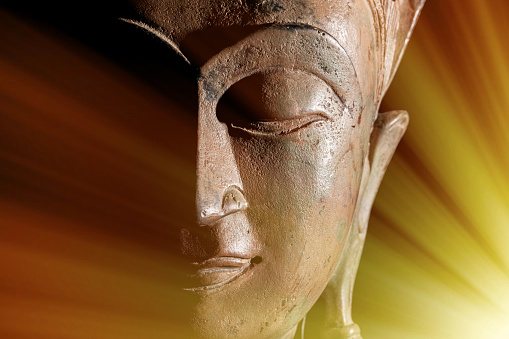 istock Zen Buddhism. Divine light rays of spiritual enlightenment or astral projection on buddha head statue. 857116892