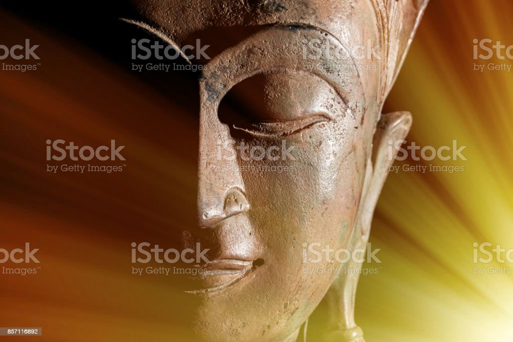 Zen Buddhism. Divine light rays of spiritual enlightenment or astral projection on buddha head statue. stock photo