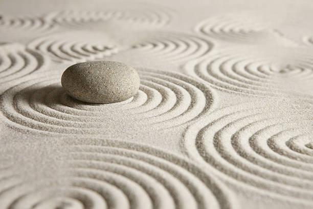 Zen garden Beige round stone on carefully arranged sand stock photo