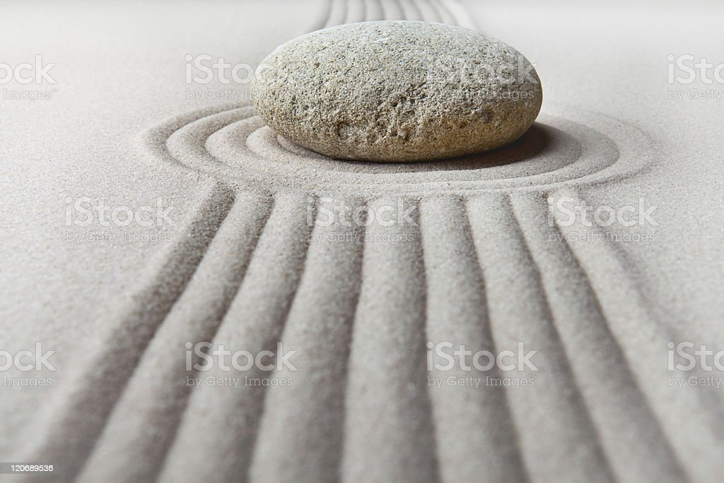Zen garden with sand pattern and rock stock photo