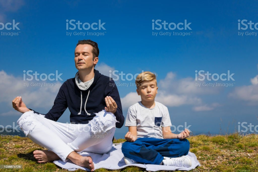 Peaceful father and son exercising Yoga with eyes closed and...