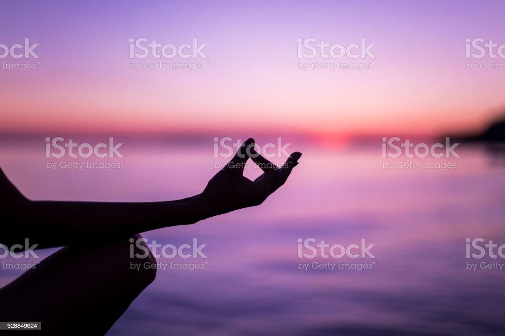 Woman Meditating On Beach Faced Towards Majestic Sunset