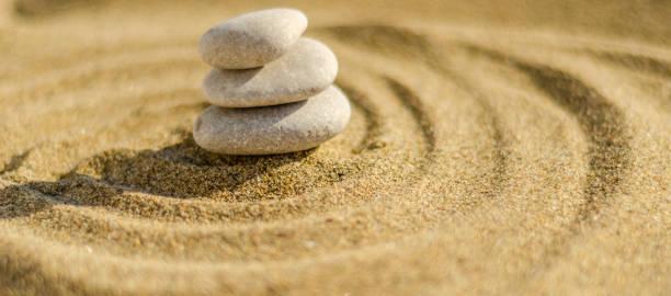 pedra de meditação Zen na areia, o conceito de harmonia de pureza e espiritualidade, wellness spa e fundo de ioga - foto de acervo