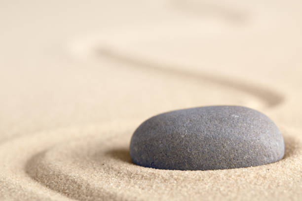 zen meditation stone with raked line in sand - spa belgium stock photos and pictures
