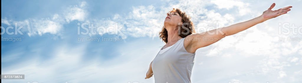 zen middle aged yoga woman opening up her chakra, banner stock photo