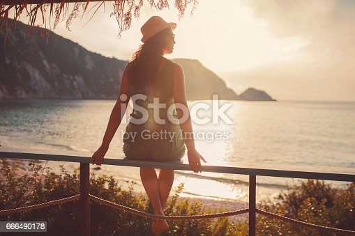 Rear view of a young caucasian woman sitting on the terrace of a beach house and enjoying the sea view.