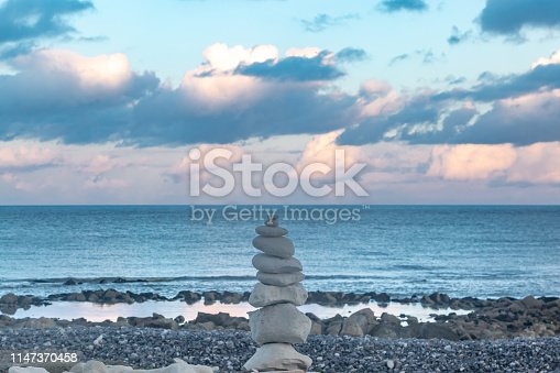 A pile of zen rocks on a pebble beach in Sussex, with the ocean behind and an evening sky overhead
