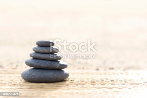 Five smooth stones on a bamboo mat.