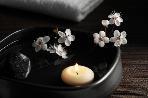 SEVERAL MORE IN THIS SERIES.  Floating aromatherapy candle with cherry blossoms and black stone in a serene zen-style spa.  Shallow DOF.