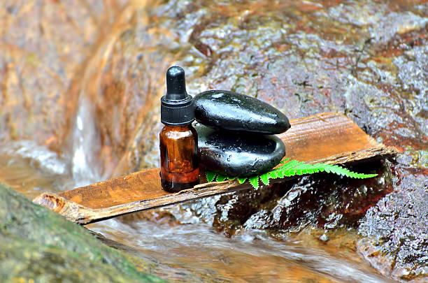 zen stone with spa oil in spa concept at waterfall - steingut geschirr stock-fotos und bilder