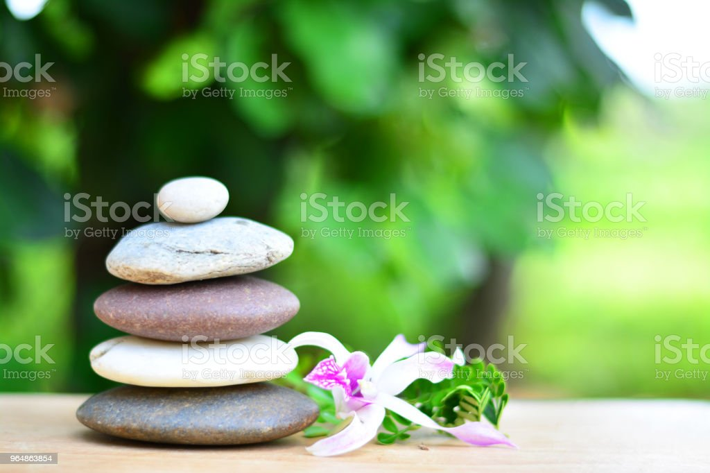 Zen stones and orchid on wooden floor with green leaves background. royalty-free stock photo