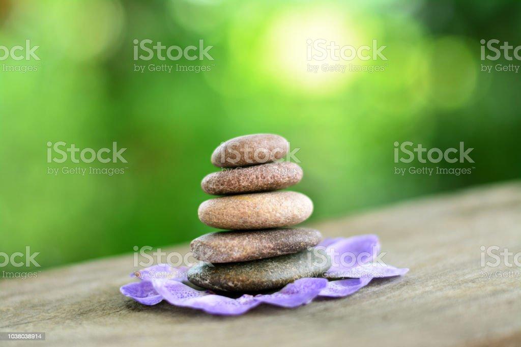 Zen stones and violet corolla on wooden floor seem like lotus with...