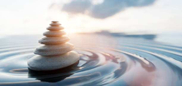 Zen stones arranged in pyramid balanced on water. Spa calm harmony stock photo
