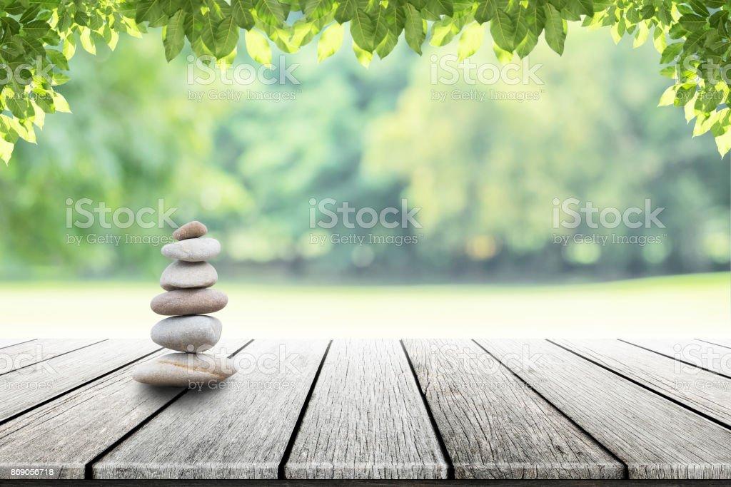 Zen stenen op lege houten met groene blad in de tuin achtergrond wazig. foto