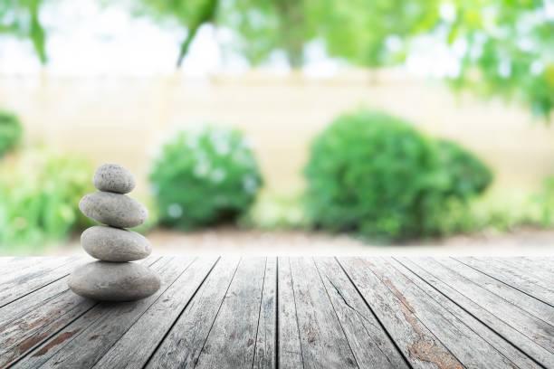 zen-steine auf holz in japanischer gartenquelle jahreszeit. - naturstein terrasse stock-fotos und bilder