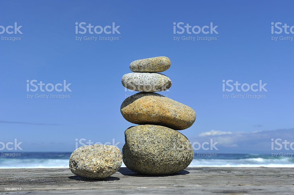 Zen stones stacked at beach waves blue sky copy space royalty-free stock photo