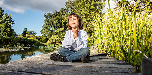 zen young yoga child meditating alone to breathe near water – Foto