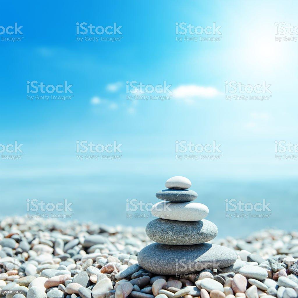 zen-like stones on beach and sun in sky stock photo