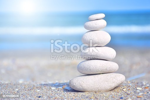 istock Zen-like stones on beach under sun 909449606