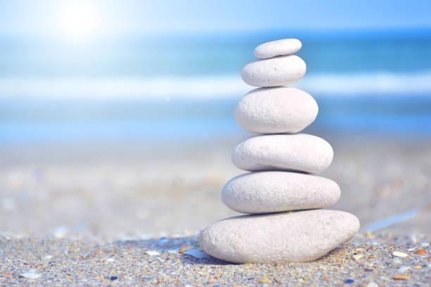 Zen-like stones on beach under sun stock photo