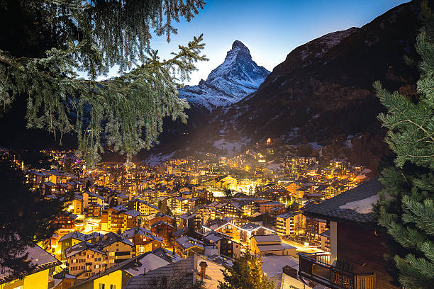 Zermatt and Matterhorn framed by the branches Warm window lights from the swiss alpine village of Zermatt light the valley at twilight with the Matterhorn peak above it zermatt stock pictures, royalty-free photos & images