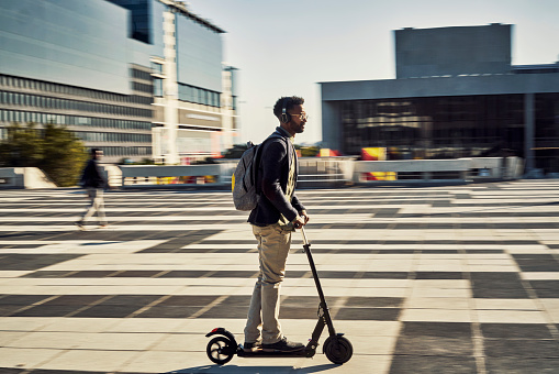 Full length shot of a handsome young businessman travelling to work on his electric scooter