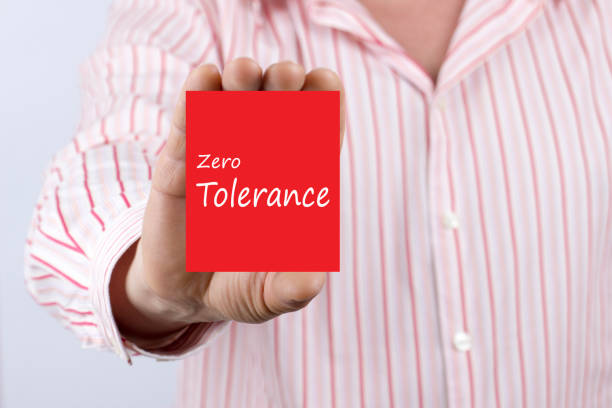"Zero Tolerance written on card Male hand showing card with text ""Zero Tolerance"" message.Defocused chart background. prettige verrassingen stock pictures, royalty-free photos & images"
