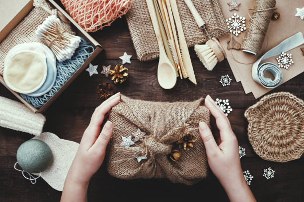 Zero waste christmas. Female hands hold gift wrapped in burlap. Eco friendly products laid out on table stock photo