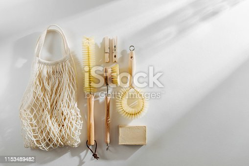 1169442284 istock photo Zero waste, compostable cleaning tools. Wooden dish brush, clothespins, soap and mesh market bag . Eco friendly concept. 1153489482