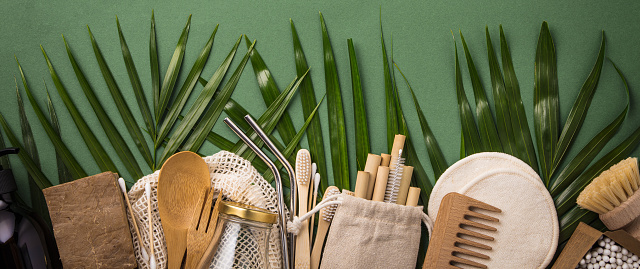istock Zero waste concept. Cotton bag, bamboo cultery, glass jar, bamboo toothbrushes, hairbrush and straws on green background 1187346339
