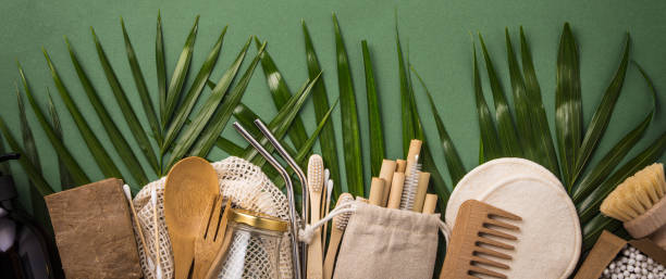 Zero waste concept. Cotton bag, bamboo cultery, glass jar, bamboo toothbrushes, hairbrush and straws on green background stock photo