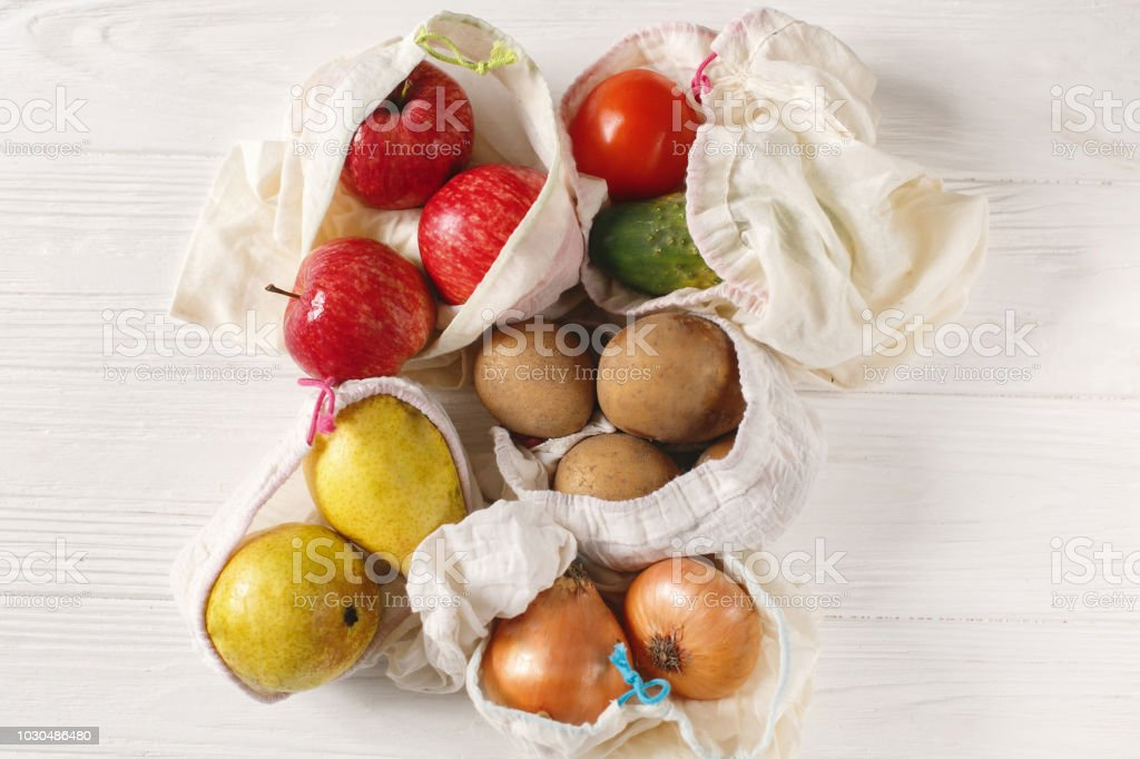 zero waste food shopping. eco natural bags with fruits and vegetables, eco friendly, flat lay. sustainable lifestyle concept.  plastic free items. reuse, reduce, recycle, refuse. groceries in eco bags stock photo