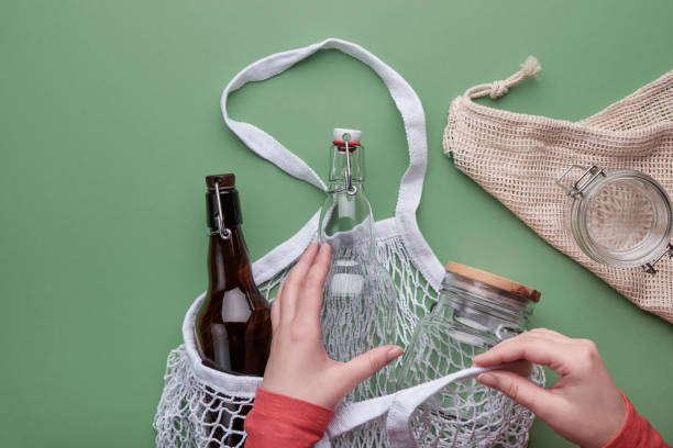 Zero waste grocery shopping concept. Hands packing glass bottles and jar in mesh bag. Top view, green background stock photo
