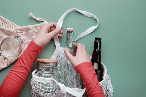 Zero waste grocery shopping concept. Hands packing glass bottles and jar in mesh bag. stock photo