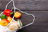 Zero waste grocery shopping. Package-free food on dark wooden table with texture. Fresh vegetables and fruits in Eco cotton bags. Plastic-free package