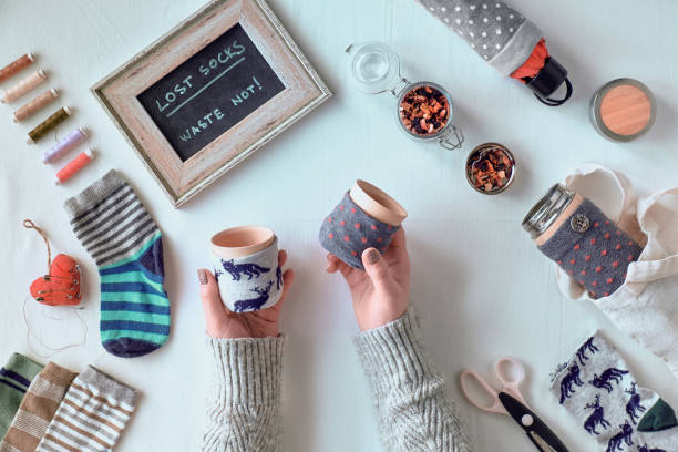 Zero waste household. Making bamboo cup and thermos can sleeve out of stray socks. Upcycle of single mismatched socks. Flat lay on textile tablecloth. Low impact sustainable lifestyle. stock photo