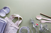 Zero waste concept - overhead still life of reusable metal boxes, canvas bags and glass jars with steel buckle.