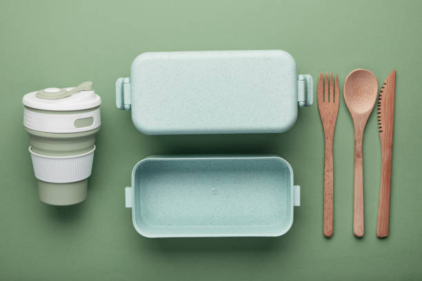 Zero waste lunch concept. Reusable cup and box, bamboo cutlery. Flat lay on green background Zero waste lunch concept. Reusable cup and box, bamboo cutlery. Flat lay on green background cutlery stock pictures, royalty-free photos & images